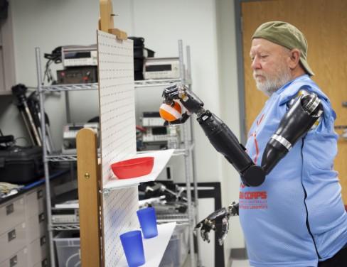 Les Baugh manipule des objets pour apprendre à mieux maîtriser ses nouvelles prothèses.
